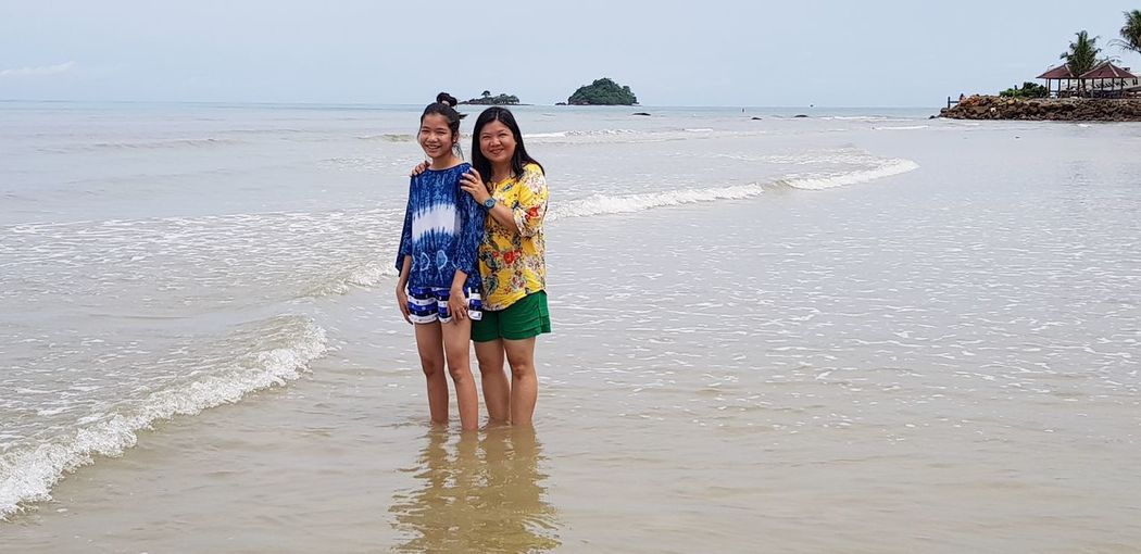 Portrait of mother and daughter standing at beach