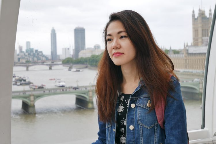 Portrait of beautiful woman standing in city against sky