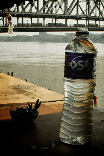 Close-up of bottle on table at sea shore