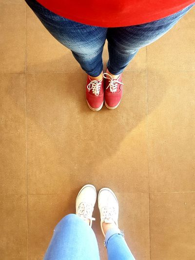 Low section of women standing on tiled floor