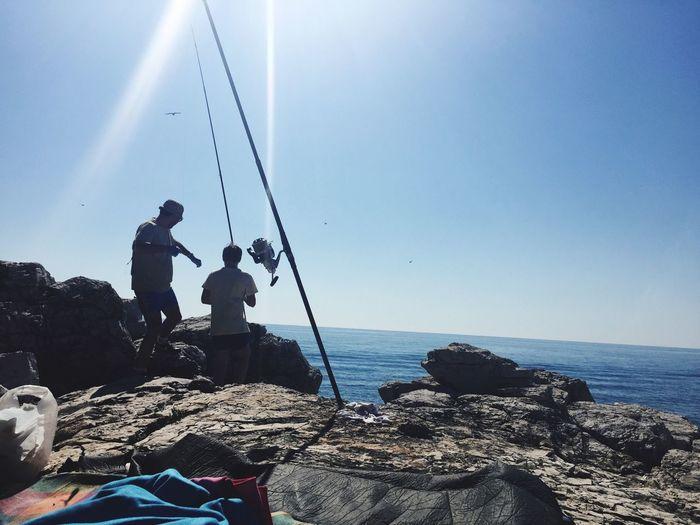 Men fishing at sea shore against clear sky