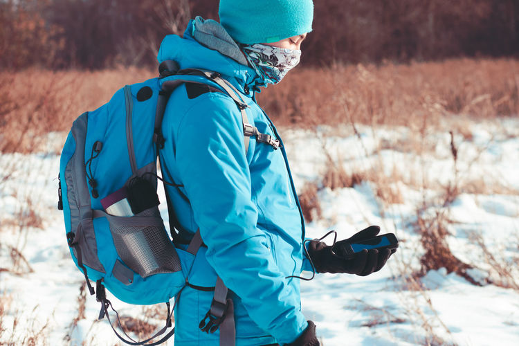 Woman looking at mobile phone in winter landscape
