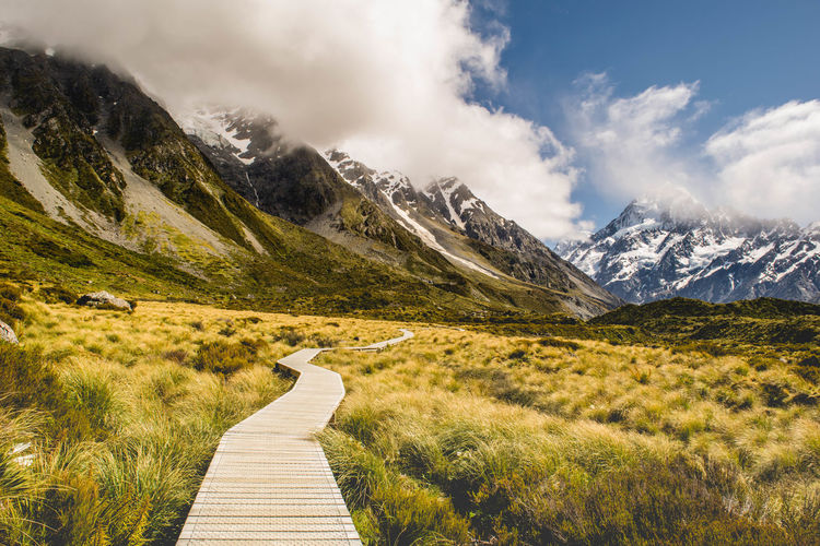 Boardwalk leading towards mountains against sky