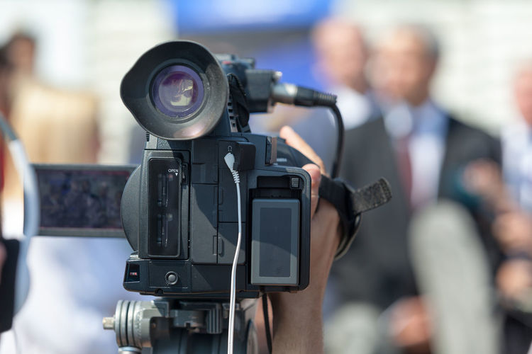 Close-up of video camera against people