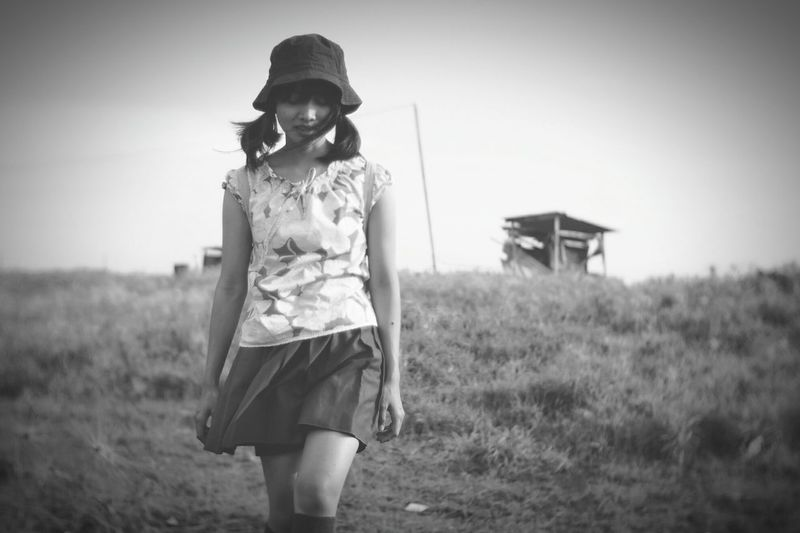 Young woman wearing hat while walking on field against sky