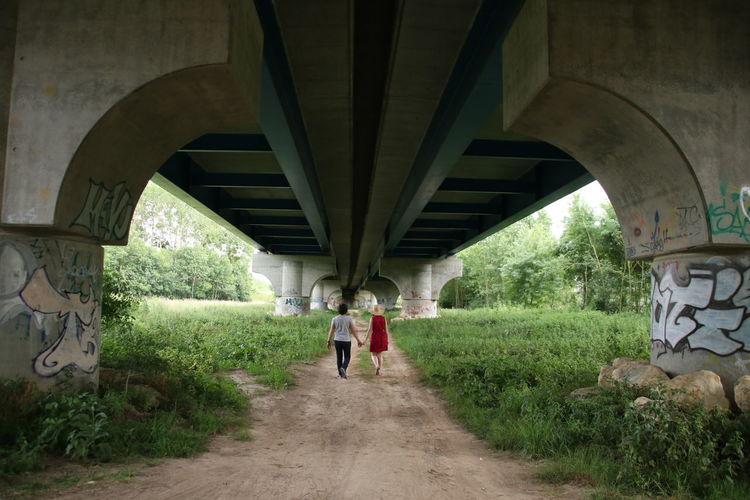 Rear view of people walking under bridge