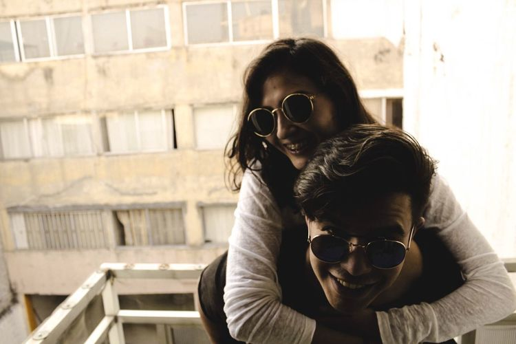Portrait Of Happy Man Piggybacking Girlfriend At Balcony
