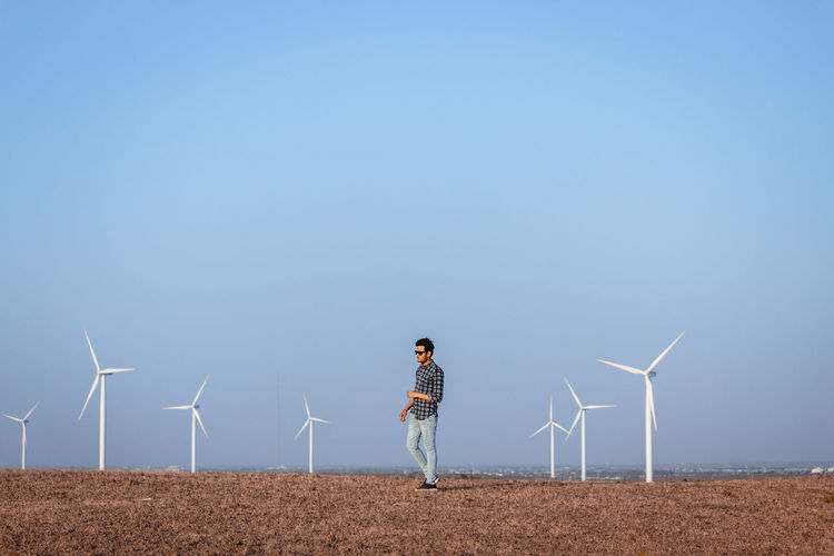 Man walking against wind turbines on field