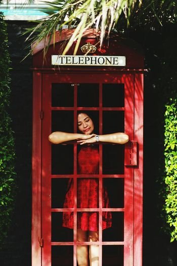 Woman standing in telephone booth