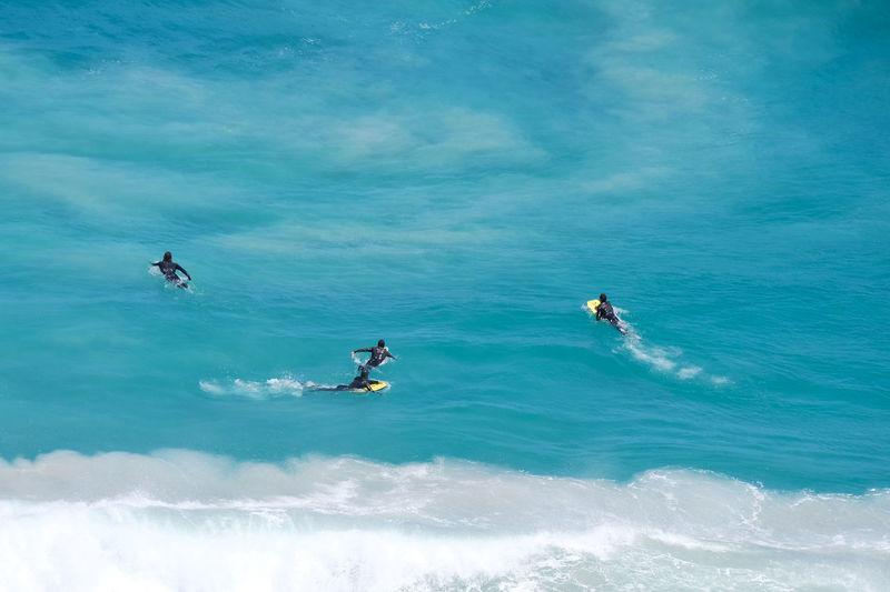 People paddleboarding in sea