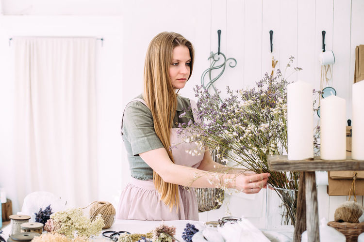 Smiling young woman making flower bouquet while standing by table at shop