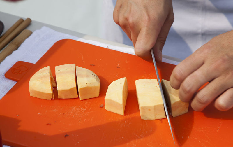 Midsection of chef cutting sweet potato on board
