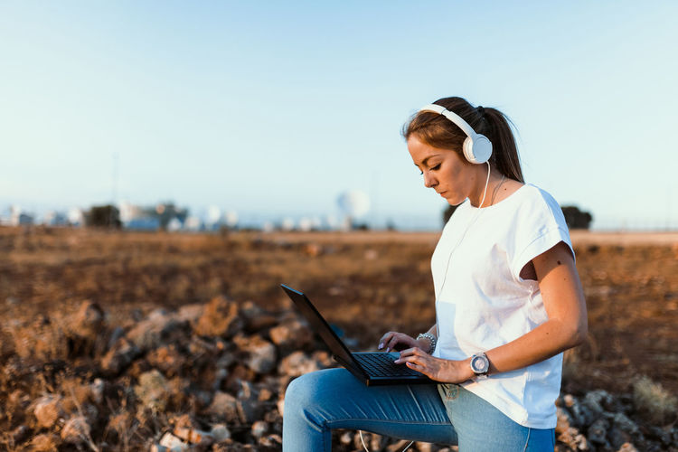 Young woman using laptop on land against sky