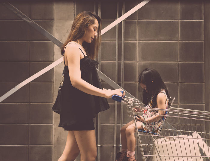 Mom Places daughter In Shopping Cart Real People Young Adult Women Hair Young Women Standing Three Quarter Length Beautiful Woman Railing Beauty People Side View Lifestyles Adult Holding Wall - Building Feature Architecture Casual Clothing Hairstyle