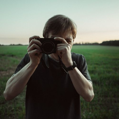 Portrait of man photographing on land