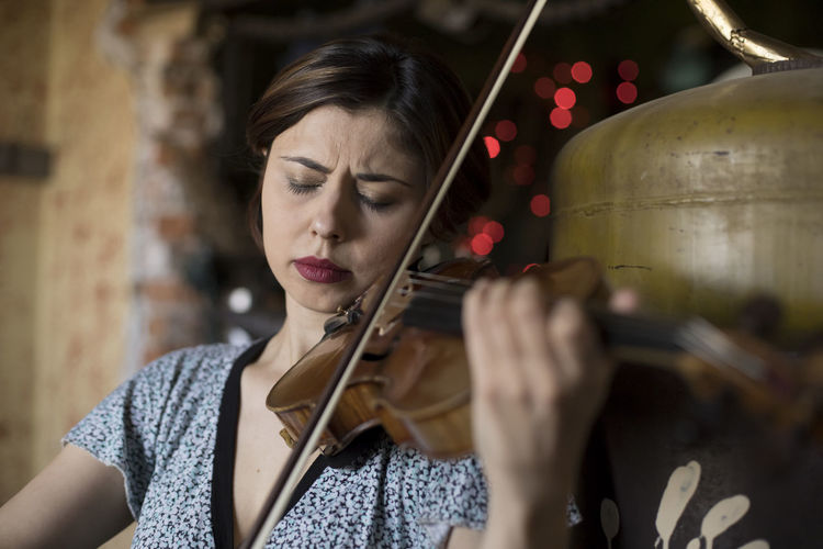 Close-up of woman with eyes closed playing violin