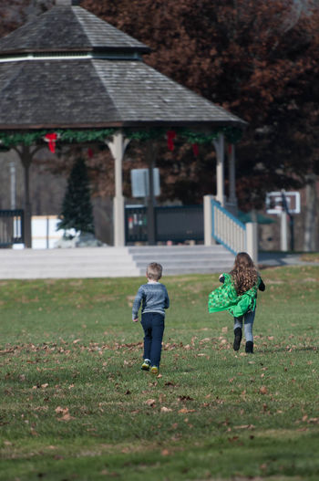Young Boy and Girl Running Through a Park Brother Family Relationship Running Sister Young Architecture Bonding Boy Built Structure Child Childhood Elementary Age Friendship Full Length Girl Outdoors People Playing Real People Togetherness Two People