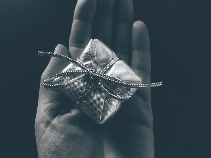 Close-up of hand holding gift over black background