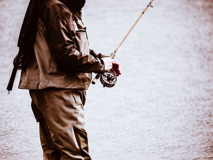 Midsection of man holding fishing rod by lake