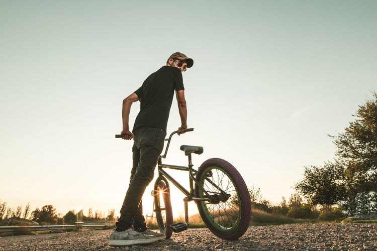 Low angle view of young man with bicycle standing on field against clear sky during sunset