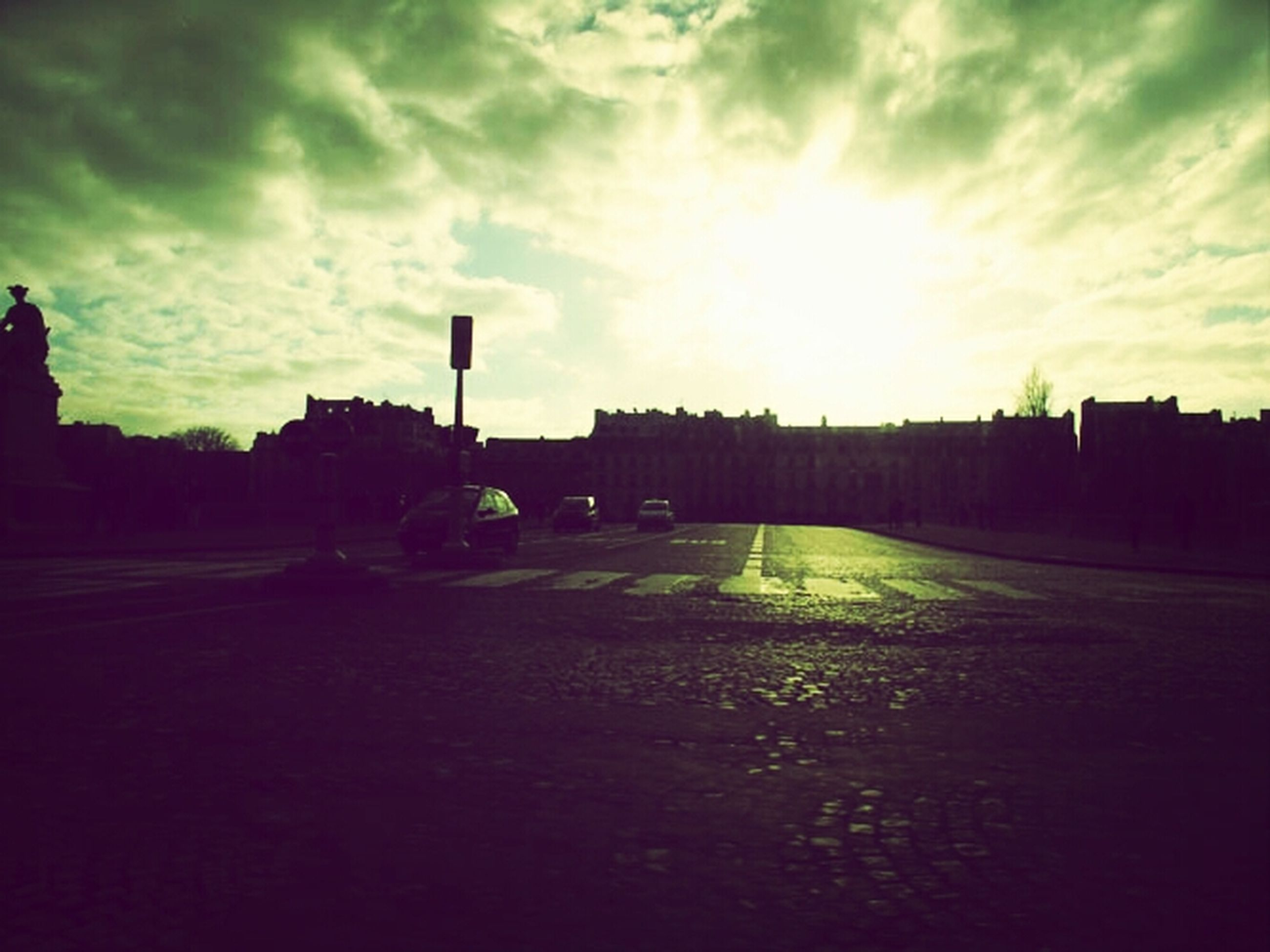 sunset, sky, silhouette, road, transportation, cloud - sky, street, sunlight, sun, the way forward, cloud, car, built structure, building exterior, architecture, sunbeam, street light, cloudy, land vehicle, outdoors
