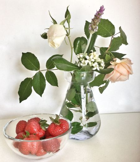 Close-up of strawberries in bowl with flower vase