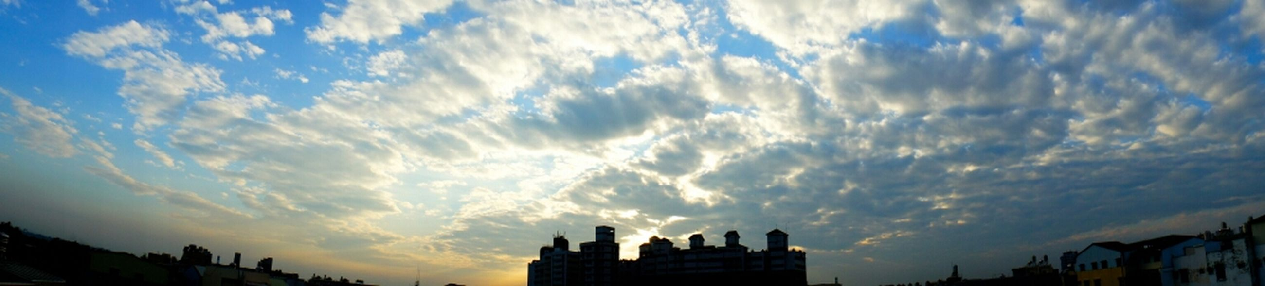 building exterior, architecture, sky, built structure, silhouette, cloud - sky, sunset, low angle view, city, cloud, cloudy, beauty in nature, nature, sunlight, scenics, sunbeam, outdoors, blue, no people, tree