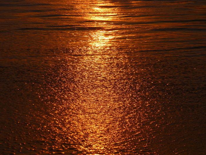 Close-up of sea waves splashing at sunset