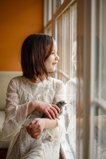 Woman looking away while sitting in window