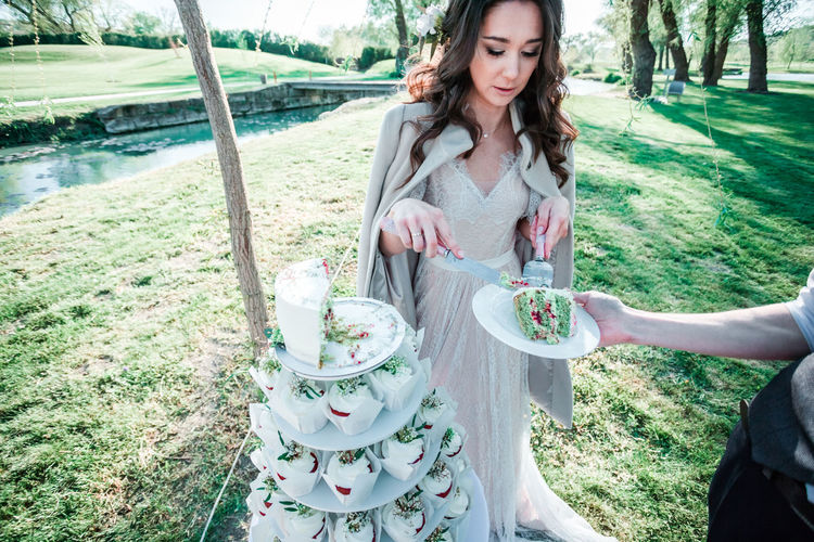 Young woman serving slice of cake at park