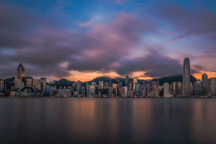 Modern skyscrapers at victoria harbour against cloudy sky