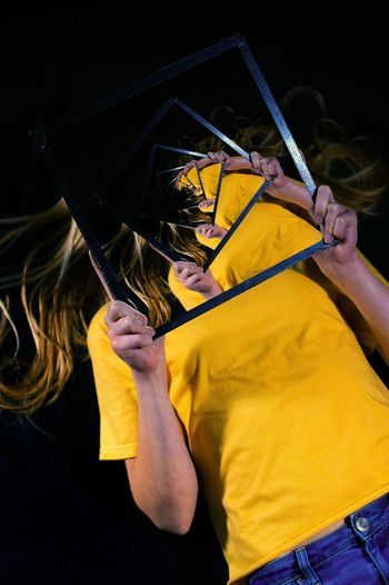 Midsection of person with yellow umbrella against black background