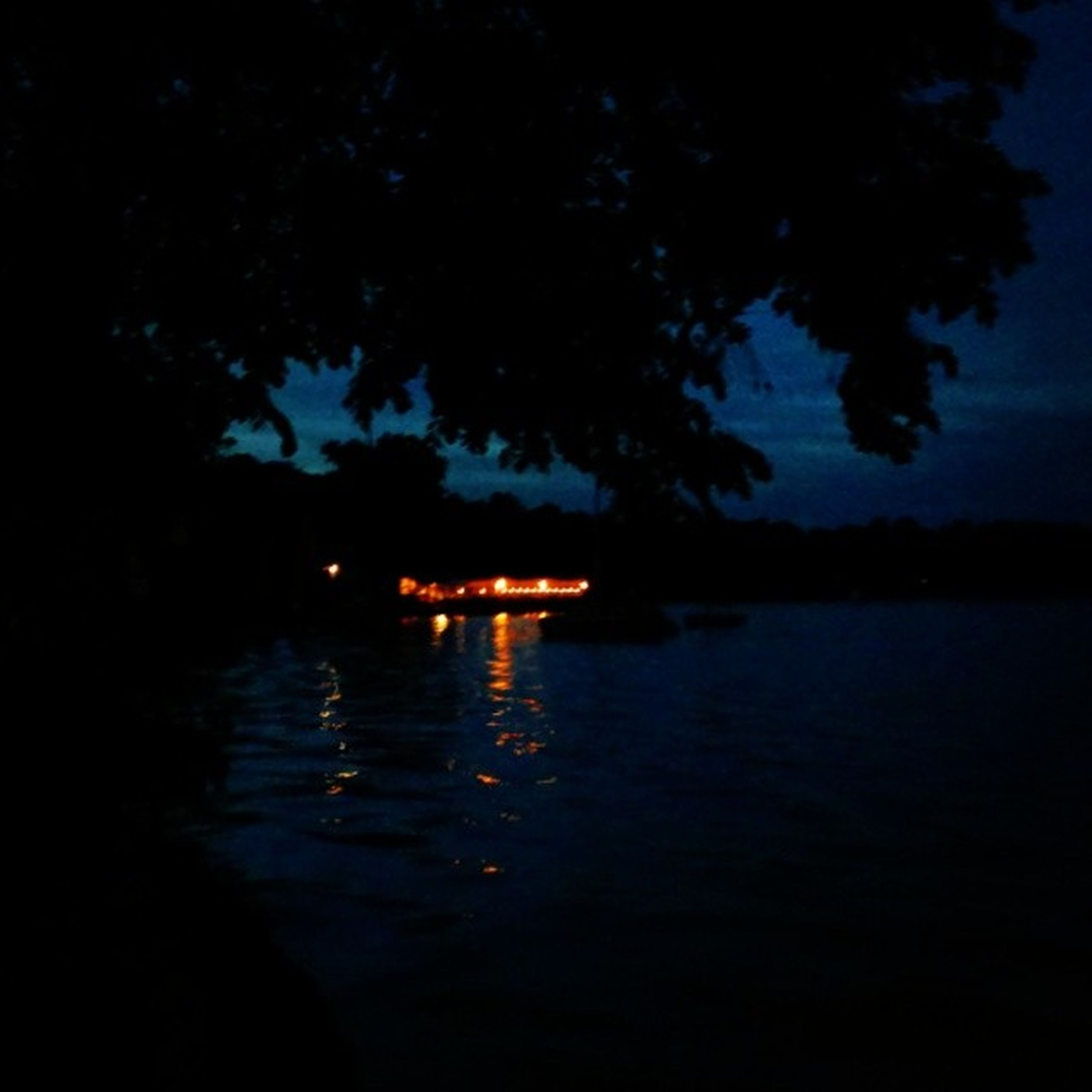 water, reflection, waterfront, night, silhouette, illuminated, sky, tranquility, lake, tree, tranquil scene, scenics, dusk, river, nature, rippled, beauty in nature, transportation, outdoors, nautical vessel