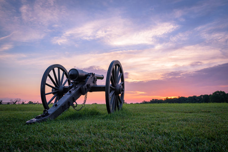 Cannon on field against sky during sunset