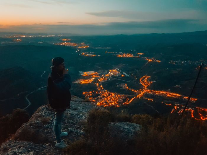 High Angle View Of Woman Standing On Cliff Against Illuminated City At Night