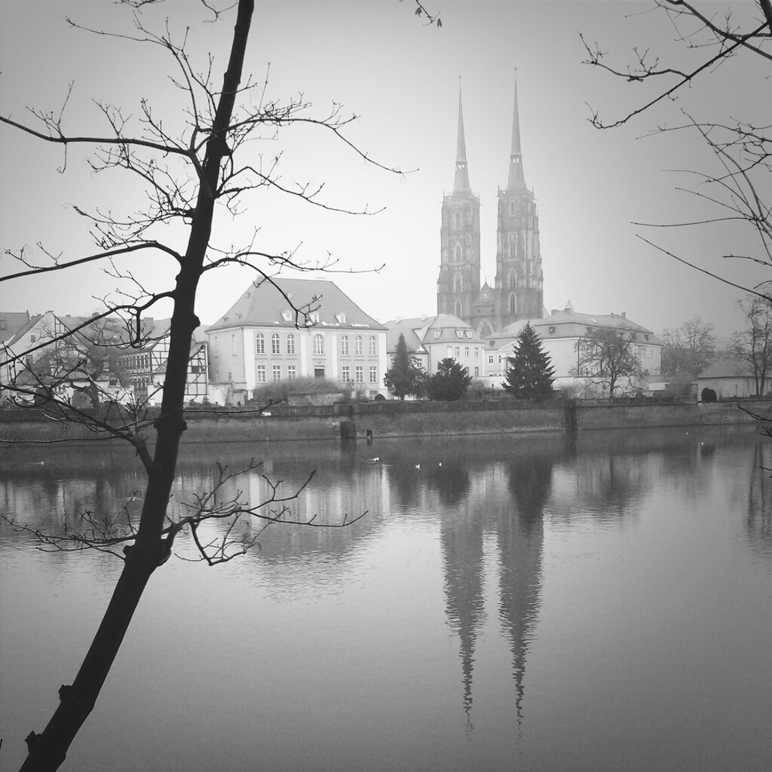 architecture, built structure, building exterior, water, reflection, city, bare tree, river, waterfront, famous place, tree, travel destinations, tower, dome, clear sky, place of worship, international landmark, church, religion, spirituality