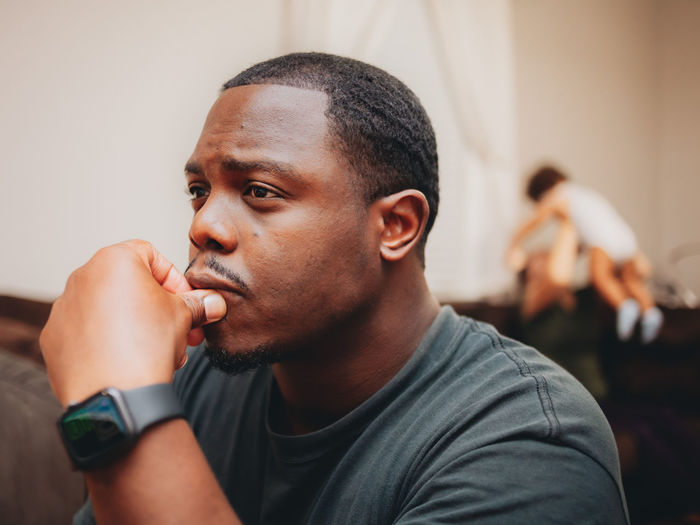 Close-up of man looking away while sitting at home