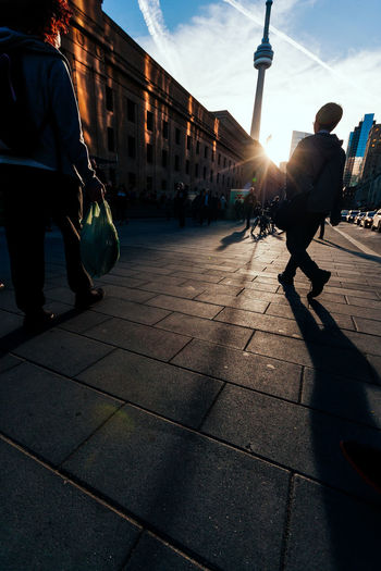People walking in city against sky during sunset
