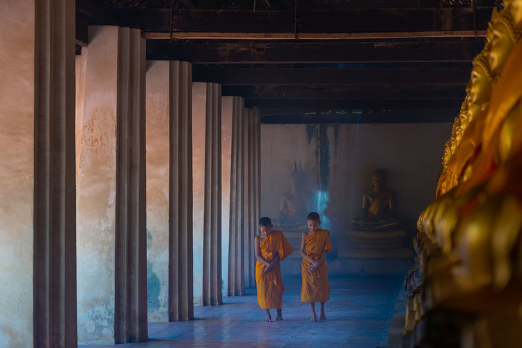 Full length of boys wearing traditional clothing walking on floor in buddhist temple