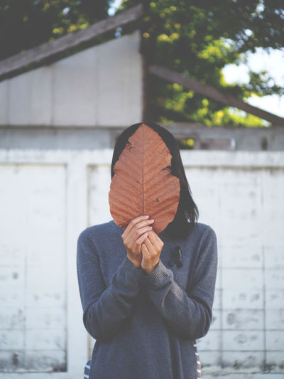 Woman covering face with dried leaf while standing against surrounding wall