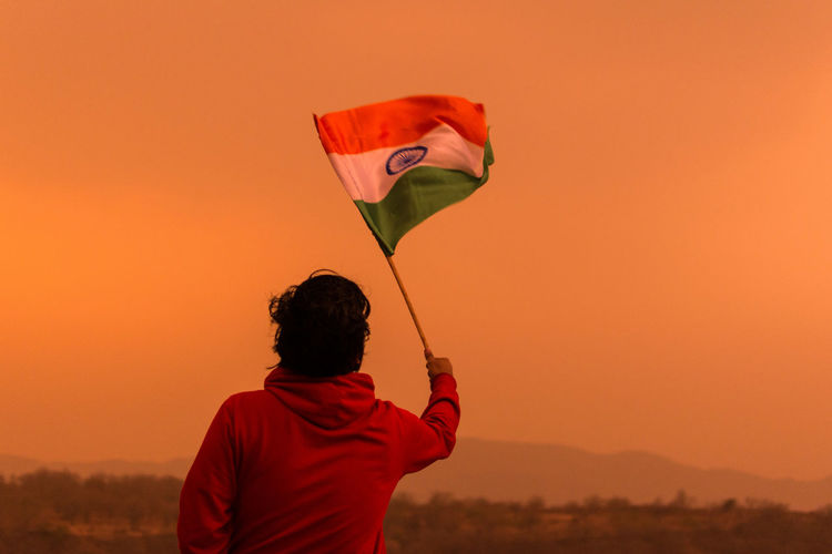 Rear view of man holding indian flag against clear sky