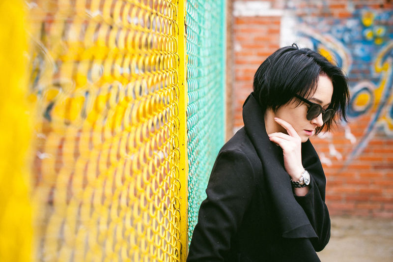 Young woman in sunglasses standing against chainlink fence