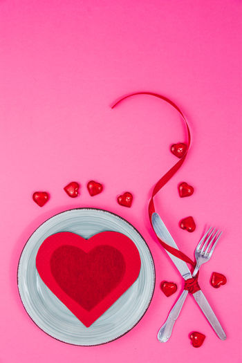 Directly above shot of heart shape on pink table