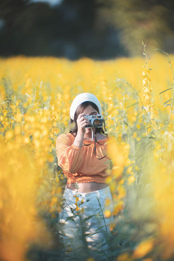 Young woman photographing on field