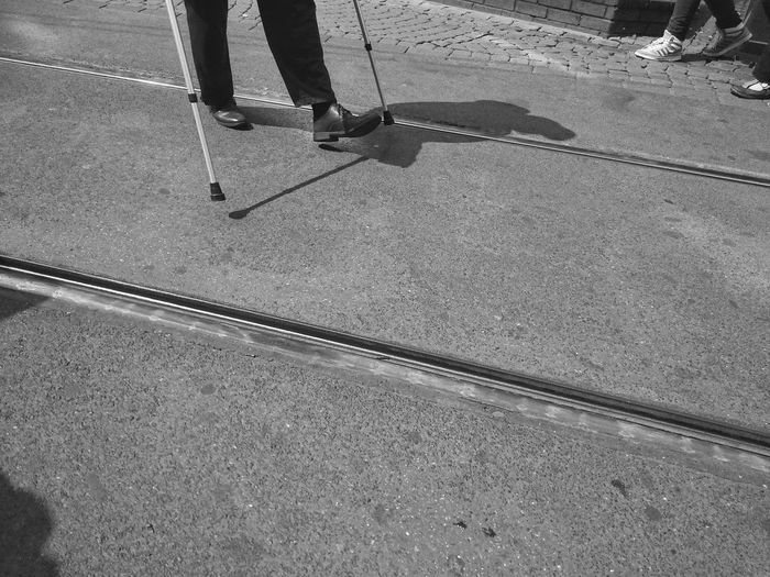 Low section of disabled man with canes walking amidst street
