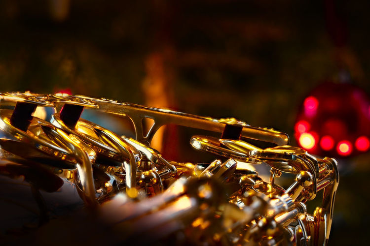 Close-up of hand of a saxophone in front of a chrismas tree