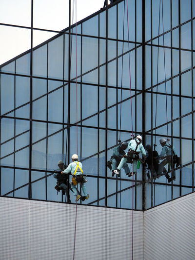 Low angle view of window washers working on modern building