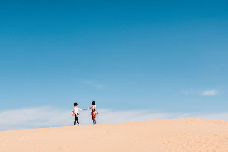 Friends standing in desert against sky
