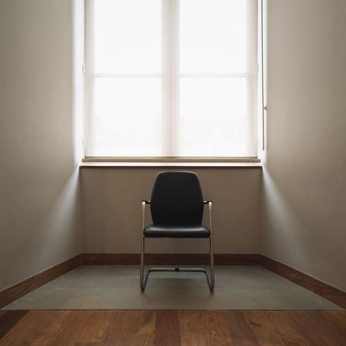 Empty chair against window