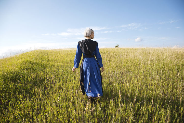 Amish woman in blue dress and black cape in a field Afternoon Amish Amish Country Apron Black Blonde Blue Bonnet Cape  Dress Field Girl Grass Pensive Religion Religious Beliefs Serious Sky And Clouds Sunlight Sunlight ☀ Walking Woman